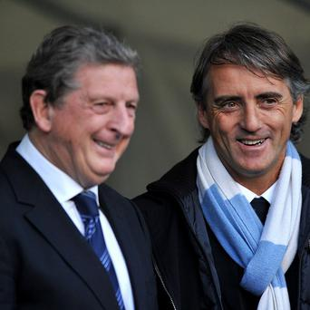 Roberto Mancini, right, is happy to help England boss Roy Hodgson, left