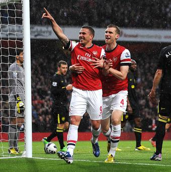 Lukas Podolski, left, scored a brace as Arsenal's victory condemned Wigan to Championship football next season