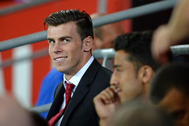 CARDIFF, WALES - AUGUST 14: Welsh international Gareth Bale, missing the game due to injury, sits on the subs bench during the International Friendly match between Wales v Ireland at the Cardiff City Stadium on August 14, 2013 in Cardiff, Wales. (Photo by Matthew Horwood/Getty Images)