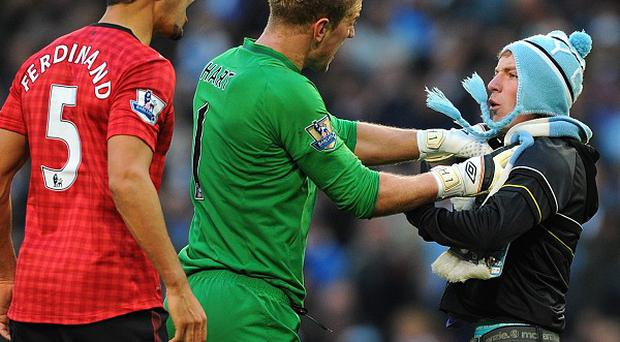 Joe Hart, centre, grabbed a supporter who ran onto the pitch in last season's Manchester derby