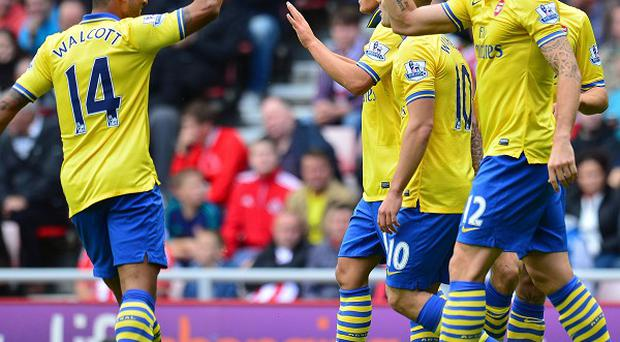 Theo Walcott, left, is aiming to win the title with Arsenal this term