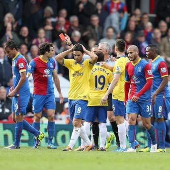 Referee Chris Foy shows Arsenal midfielder Mikel Arteta, third left, a red card