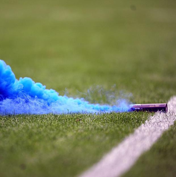 A blue flare is thrown onto the pitch during a game
