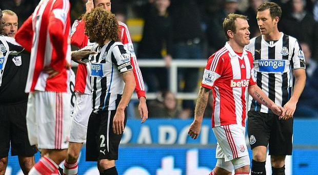 Glenn Whelan, right, is shown a red card by referee Martin Atkinson, centre
