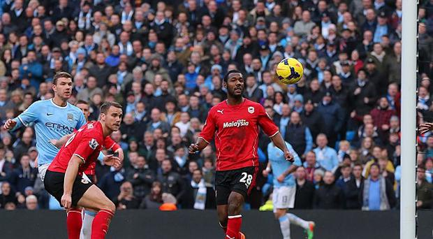 Edin Dzeko, left, scored Manchester City's 100th goal of the season in the victory over Cardiff
