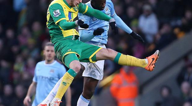 Chris Hughton believes Yaya Toure, right, should have seen red for a challenge on Ricky van Wolfswinkel, left.