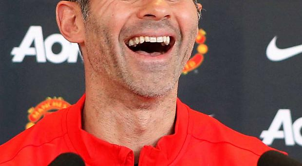 Smiling assassin: Ryan Giggs shares a joke with the media at Old Trafford yesterday