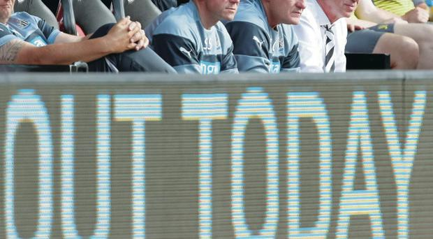 A telling sign? Alan Pardew and his backroom team peer over an advertising board as Newcastle slump to defeat at St Mary's