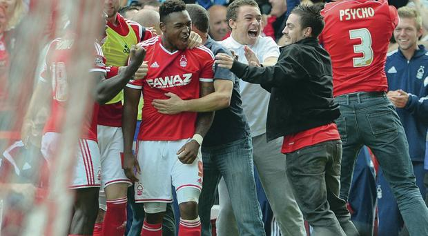 Fan-tastic: Britt Assombalonga is mobbed by Nottingham Forest supporters after putting his side ahead against rivals Derby
