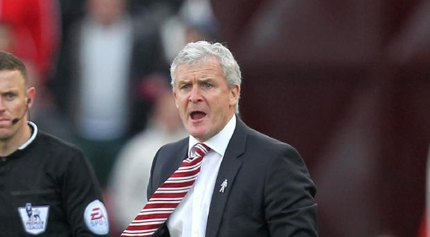 Stoke boss Mark Hughes, pictured, felt referee Chris Foy should have stopped play in the 2-2 draw with West Ham when Alex Song tackled Mame Biram Diouf.
