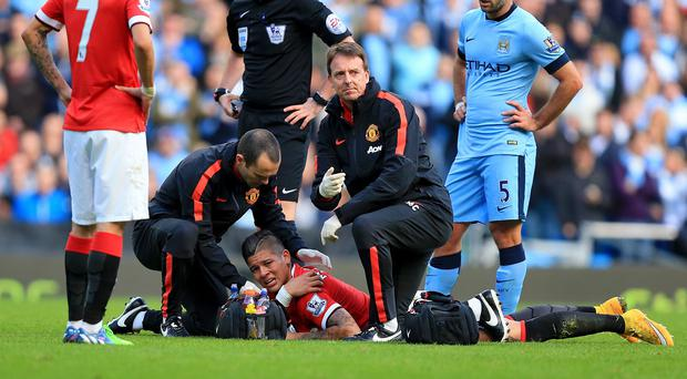 Marcos Rojo, bottom, had to be stretchered off in the Manchester derby