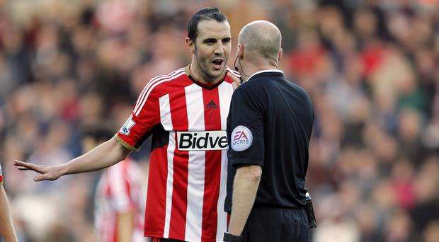 John O'Shea leads Sunderland's protests after the penalty decision