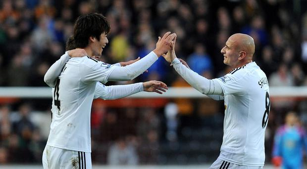 Swansea's Ki Sung-Yueng, left, celebrates after scoring against Hull City