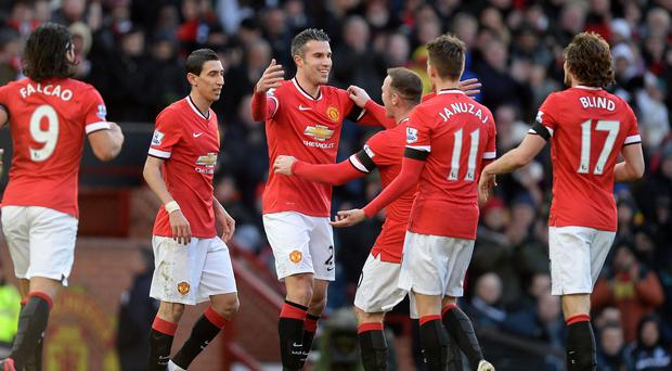 Van Persie celebrates with his United team-mates after scoring the opener at Old Trafford