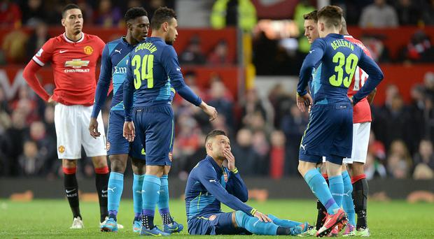 Alex Oxlade-Chamberlain, seated, was injured during the FA Cup win at Old Trafford