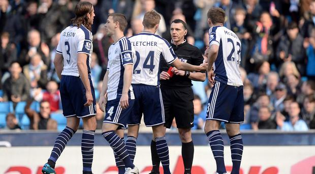 Referee Neil Swarbrick wrongly sent off West Brom's Gareth McAuley, right,