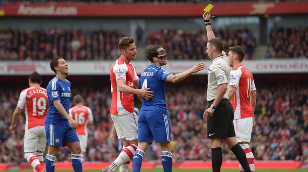 Chelsea's Cesc Fabregas, centre, is shown a yellow card for diving in the penalty area
