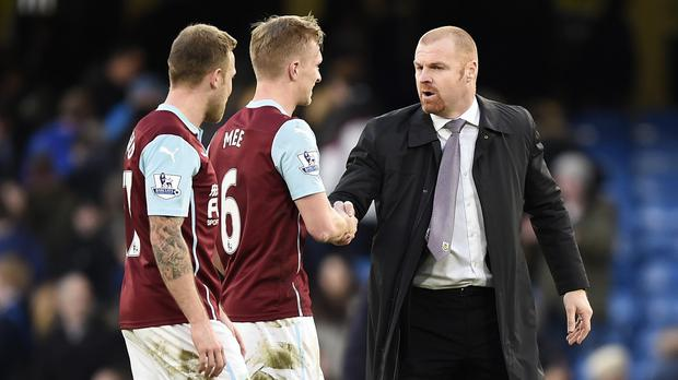 Ben Mee, centre, hopes to be playing under Sean Dyche, right, at Burnley again next season