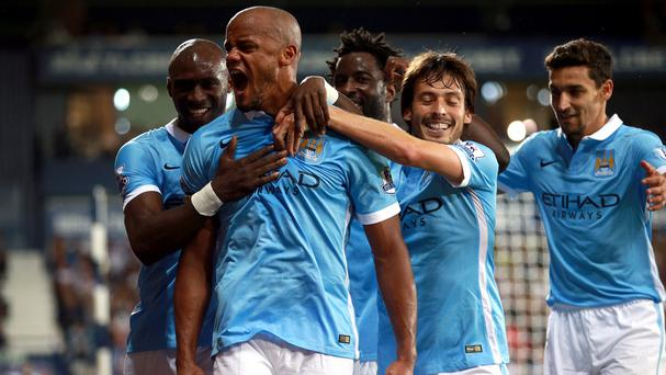 Vincent Kompany (second left) celebrates scoring his side's third goal of the game at The Hawthorns