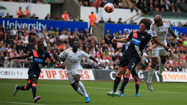Andre Ayew (right) heads in Swansea's second goal of the game against Newcastle