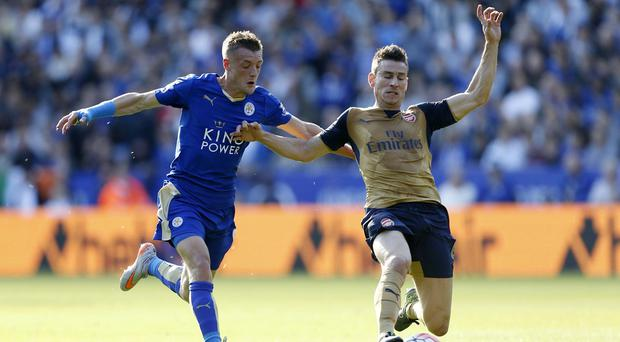 Leicester's Jamie Vardy, battling with Arsenal's Laurent Koscielny, has to wear a cast to protect his wrist