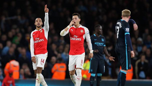 Mesut Ozil, pictured centre, fought off chest infection to guide Arsenal to a win over Manchester City