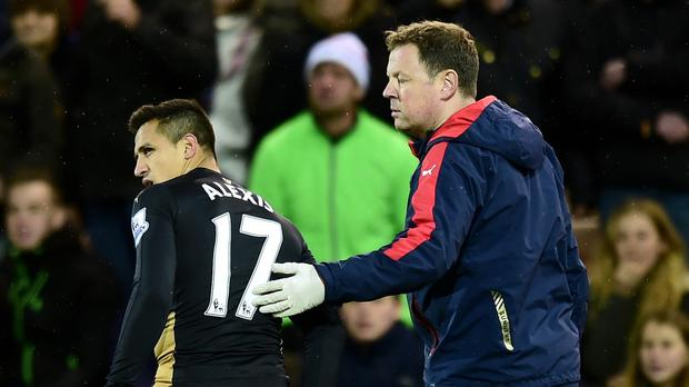 Alexis Sanchez, left, limps off injured in Arsenal's draw at Norwich on November 29