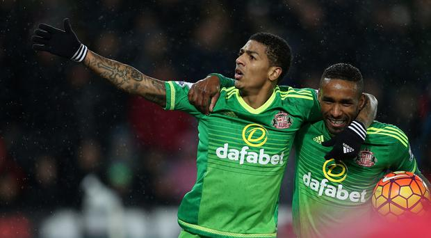 Sunderland's Patrick van Aanholt (left) and hat-trick Jermain Defoe hero celebrate in Sunderland's 4-2 Barclays Premier League victory at Swansea.