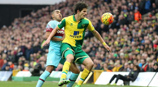 Norwich's Timm Klose (right) tussles with West Ham's Dimitri Payet (left).