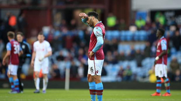 Joleon Lescott looks dejected after Villa concede their third goal against Liverpool