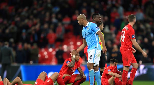 Manchester City captain Vincent Kompany, centre, consoled beaten Liverpool players after the Capital One Cup final