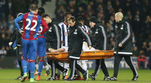 West Brom's Chris Brunt is stretchered off against Crystal Palace and is now out for six months.