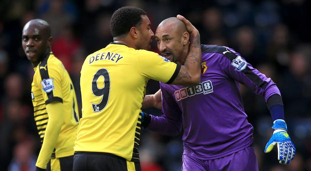 Heurelho Gomes, right, is congratulated by Troy Deeney, centre, after saving a penalty