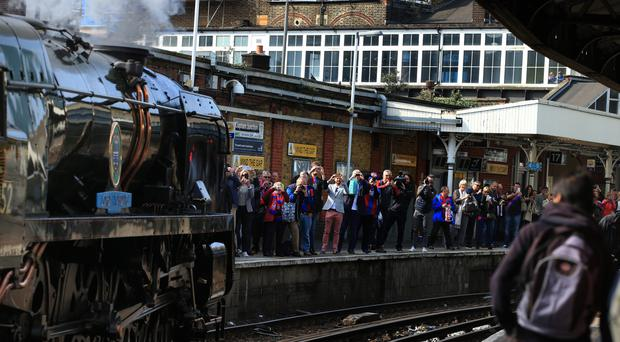 Cystal Palace fans wait on the platform at Clapham Junction for the Lord Dowding train