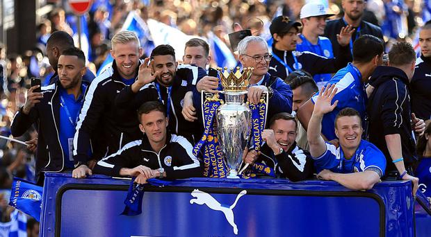 Leicester celebrate with the Premier League trophy during their open top bus parade through the city