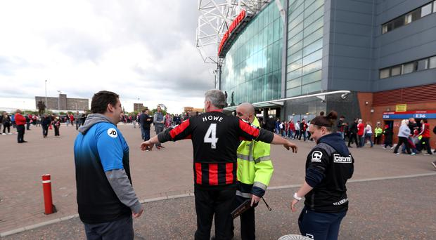 Stewards search fans in a security check before the Barclays Premier League match at Old Trafford, Manchester.