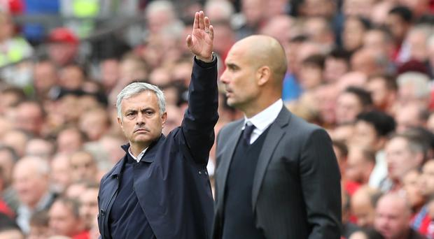 Manchester United manager Jose Mourinho, with his left hand raised, stands alongside Manchester City boss Pep Guardiola