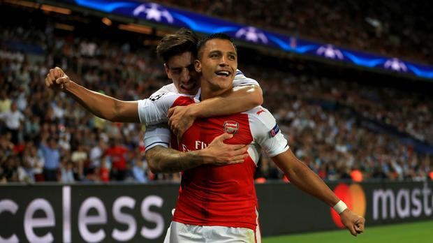 Arsenal's Alexis Sanchez (right) celebrates scoring his side's first goal of the game against PSG