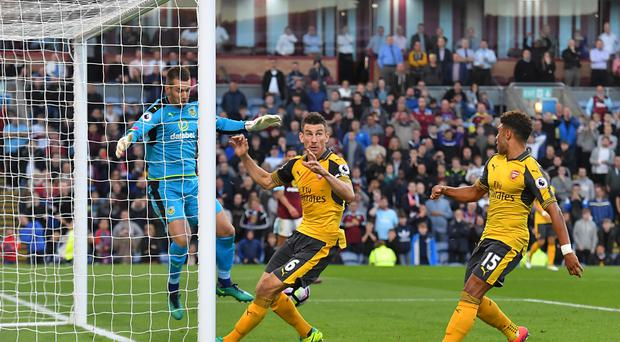 Arsenal's Laurent Koscielny (centre) is hit by Alex Oxlade-Chamberlain's (right) shot before the ball goes in.