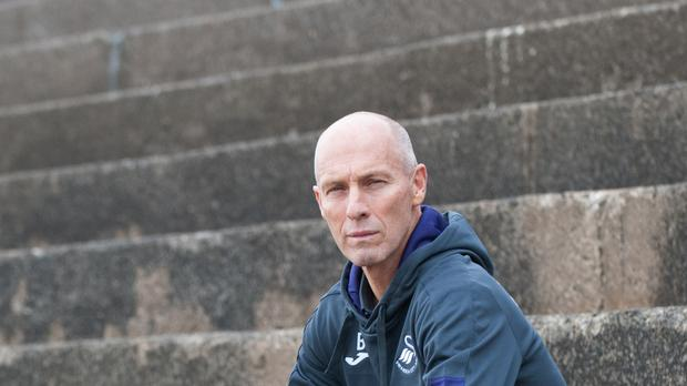 New Swansea manager Bob Bradley will come up against Arsene Wenger in his first match in charge