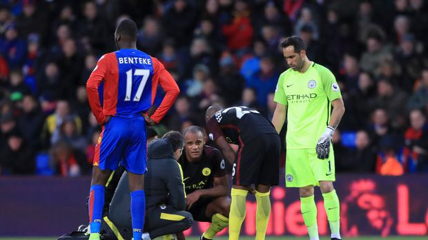 Manchester City's Vincent Kompany, crouching, receives treatment Selhurst Park