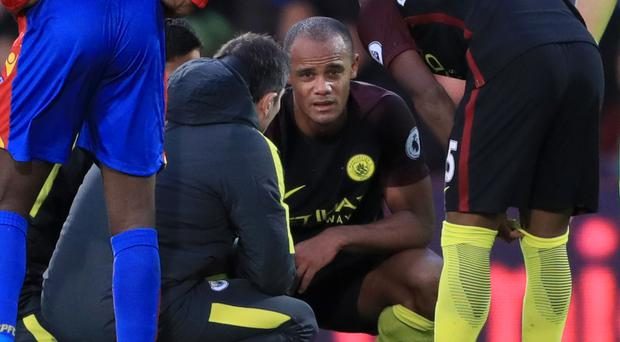 Vincent Kompany, centre, suffered a knee injury in his accidental collision with Claudio Bravo
