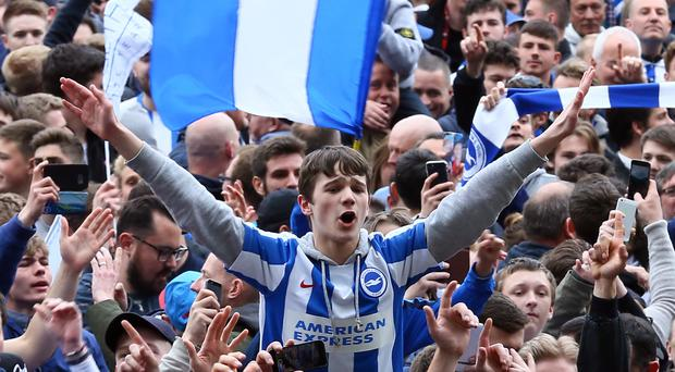 Brighton fans celebrated on the pitch at the Amex Stadium on Monday