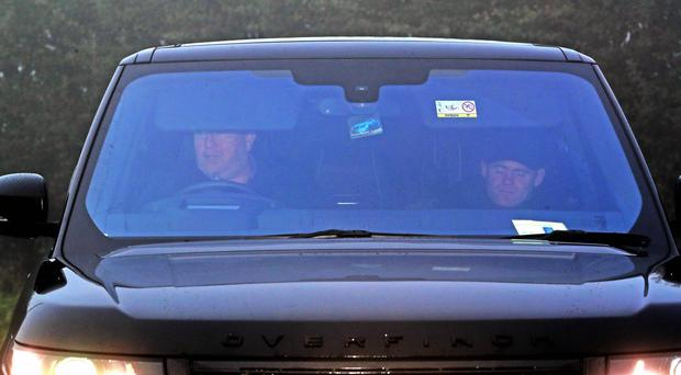 Wayne Rooney (right) is driven in to Everton's Finch Farm training ground after being banned from driving for two years.