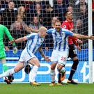 Huddersfield Town's Aaron Mooy celebrates scoring his side's first goal of the game with Laurent Depoitre (right) during the Premier League match at the John Smith's Stadium, Huddersfield.