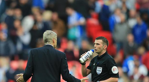 Arsene Wenger (left) was not impressed with some of Michael Oliver's decisions