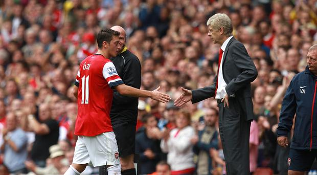 Arsene Wenger, right, has denied reports Mesut Ozil, left, has already agreed a deal to leave Arsenal