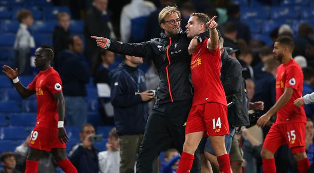 Jurgen Klopp, pictured left, believes Liverpool captain Jordan Henderson, right, has the most difficult job in football