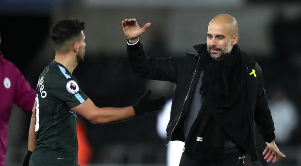 Pep Guardiola (right) celebrates Manchester City's record-breaking 15th consecutive Premier League win at Swansea with Sergio Aguero (left).