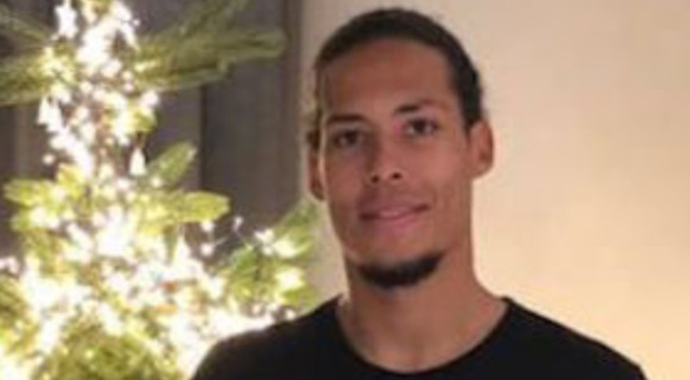 New arrival: Virgil van Dijk poses with a Liverpool jersey